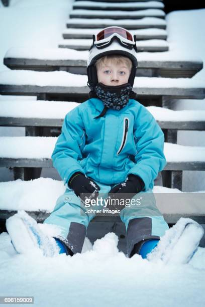Boy in skiwear sitting on steps in winter