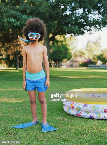 Boy (8-10) in snorkel gear standing near wading pool, portrait