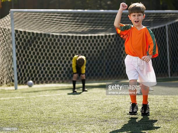 Boy in soccer uniform celebrating, defeated goalkeeper in background (portrait)