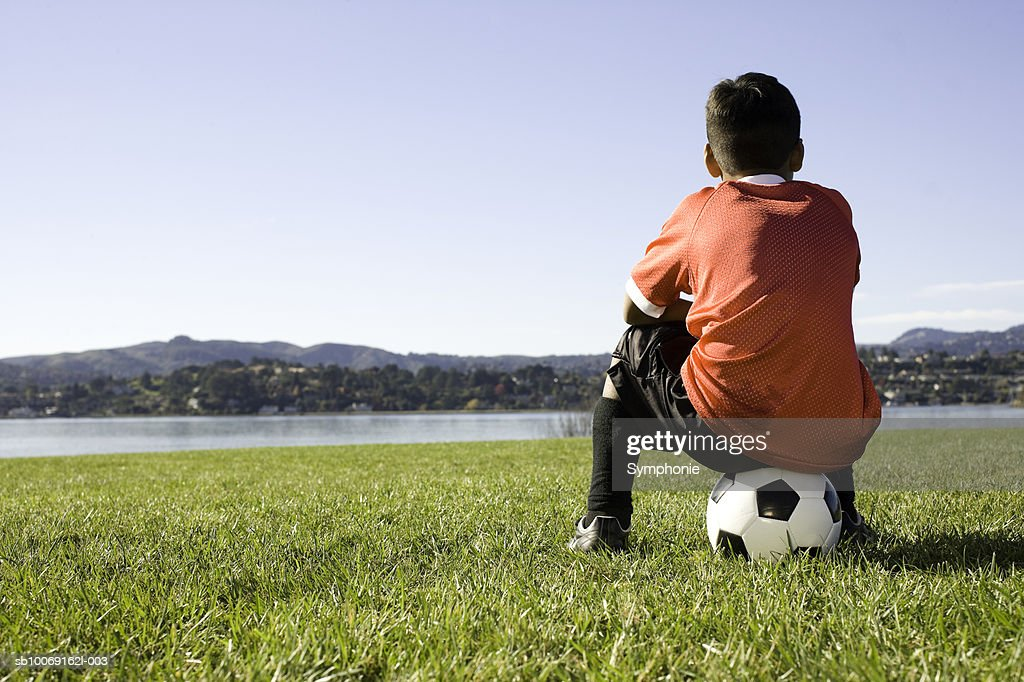 Boy in soccer uniform sitting on ball, rear view : Stockfoto