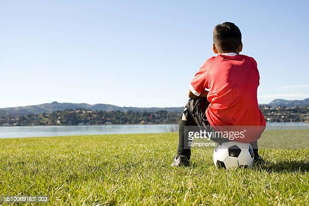 Boy in soccer uniform sitting on ball, rear view