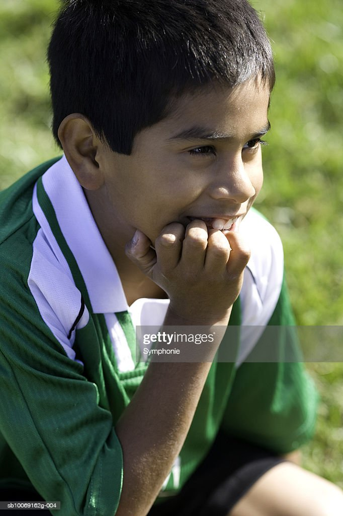 Boy in soccer uniform sitting with hand on chin, smiling, close-up : Stockfoto