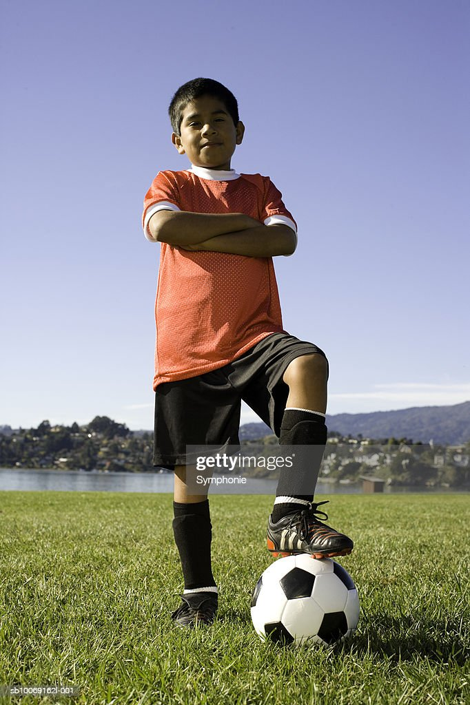 Boy in soccer uniform standing with ball, portrait : Stockfoto