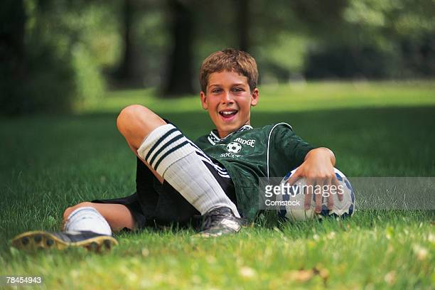 Boy in soccer uniform with ball sitting in grass