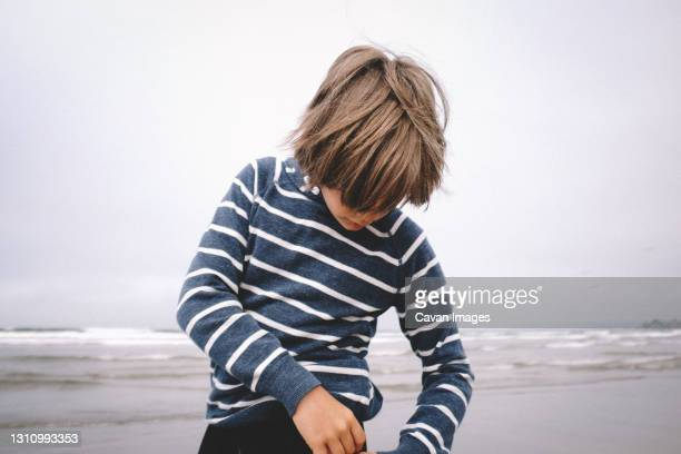 boy in striped shirt with long hair on a beach - pismo beach stock pictures, royalty-free photos & images