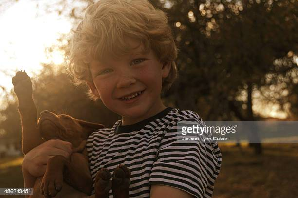 boy in stripes hugging a puppy - lynn pleasant stock pictures, royalty-free photos & images
