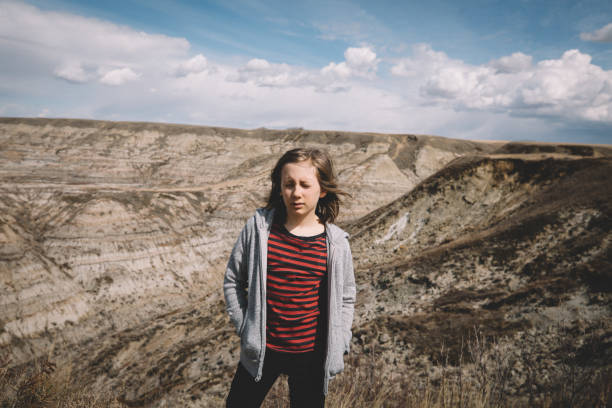 Boy in Stripes Squints into the Sun on the Edge of a Badlands