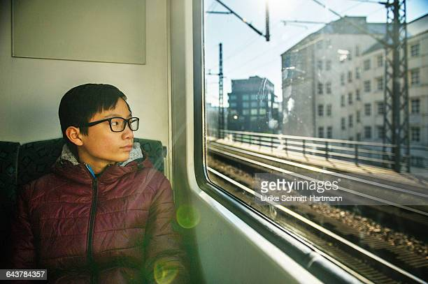 Boy in suburban train, looking out of the window