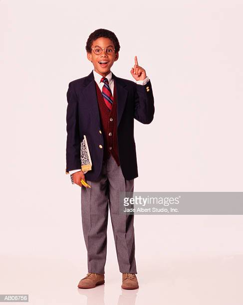 Boy (6-8) in suit carrying books