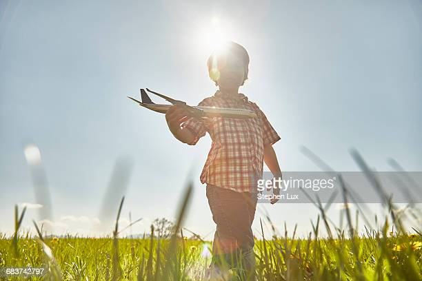 boy in sunlit field playing with toy airplane - landing touching down stock pictures, royalty-free photos & images