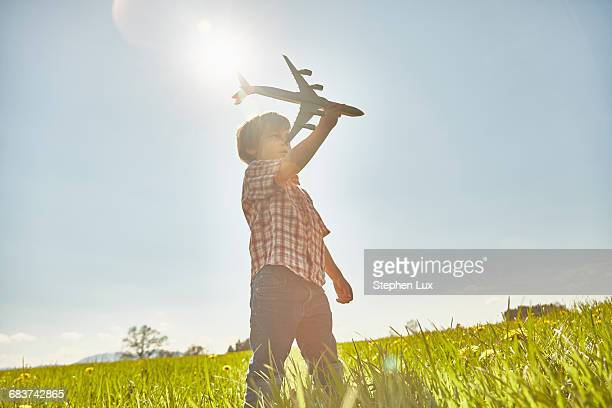 Boy in sunlit field with blue sky playing with toy airplane
