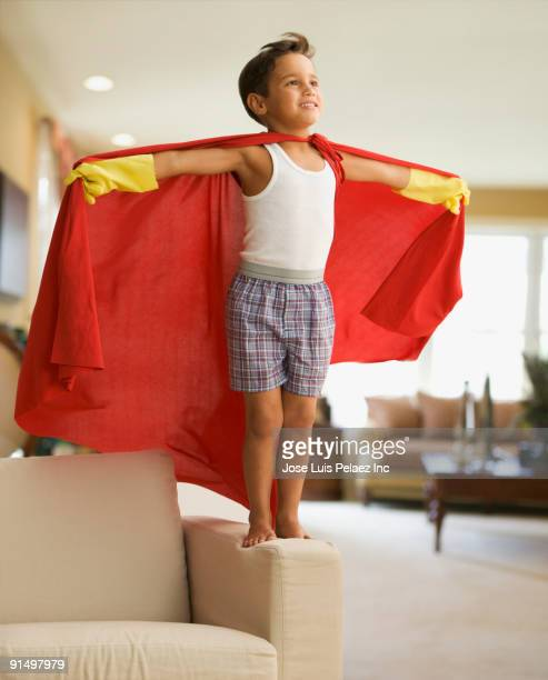 Boy in superhero costume standing on chair