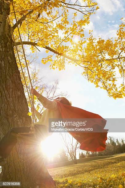 Boy in superhero costume swinging on swing