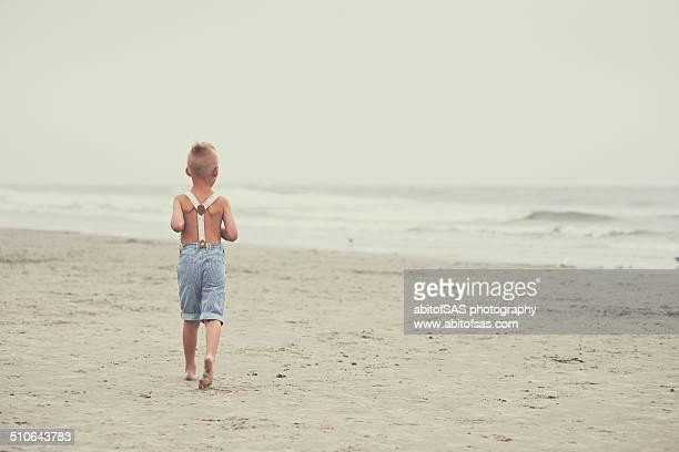 Boy in suspenders runs towards ocean
