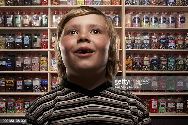 boy (6-8) in sweetshop, close-up (digital composite) - außergewöhnlich stock-fotos und bilder
