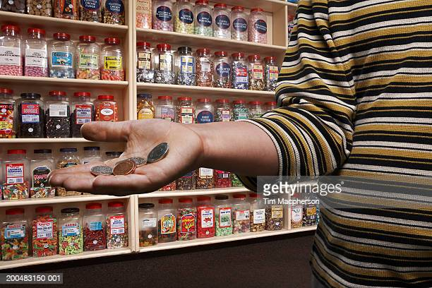 Boy (6-8) in sweetshop, holding out palm with loose change, close-up (Digital Composite)