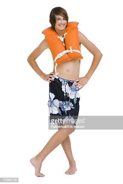 Boy in swim trunks with life vest