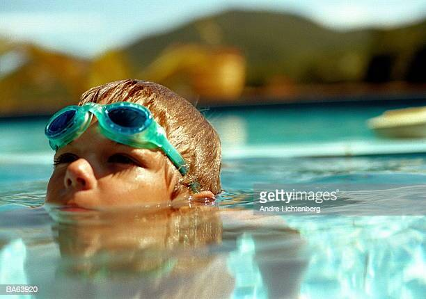 Boy (5-7) in swimming pool, close-up