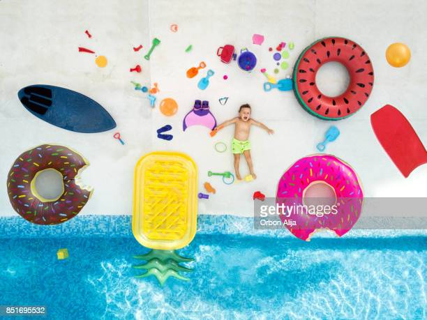 Boy in swimming pool surrounded with toys