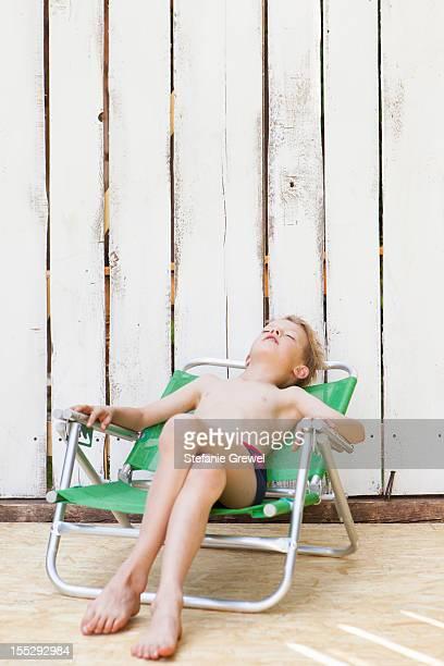 boy in swimsuit in lawn chair indoors - stefanie grewel stock-fotos und bilder