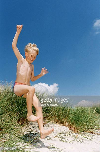 boy in swimsuit playing on beach - zwembroek stockfoto's en -beelden