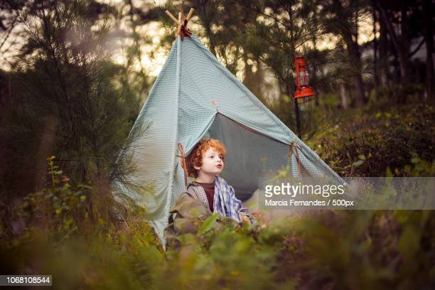 boy in teepee tent in garden - teepee stock pictures, royalty-free photos & images