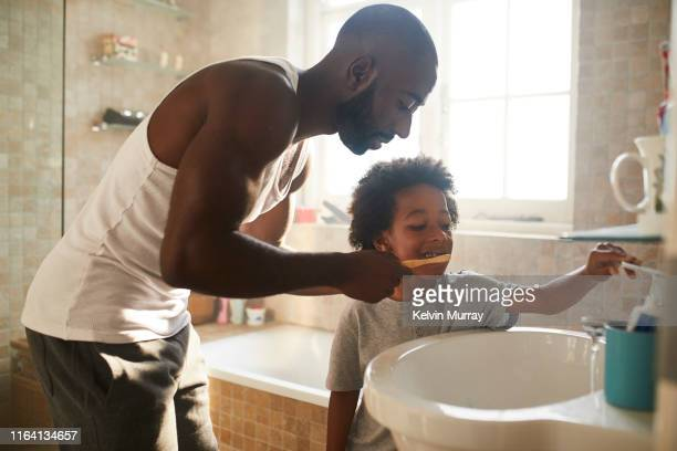 a boy in the bathroom brushing his teeth with his dad in the morning with bamboo toothbrush - genderblend stock-fotos und bilder