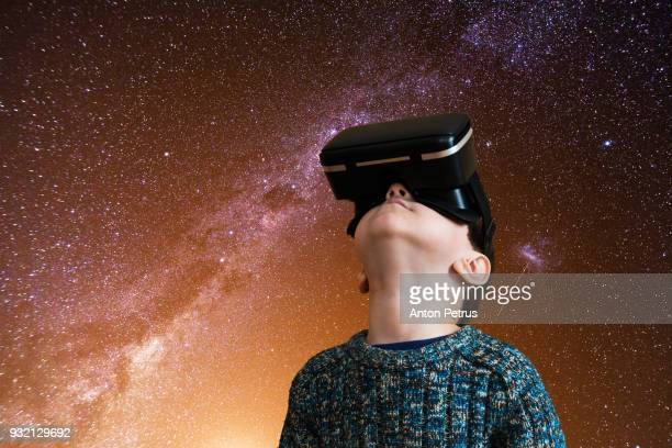 Boy in the glasses of virtual reality on a background of night sky