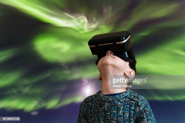 Boy in the glasses of virtual reality on a background of northen lights