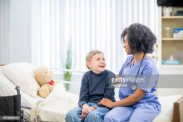 Boy in the Hospital Happily Sitting with a Nurse