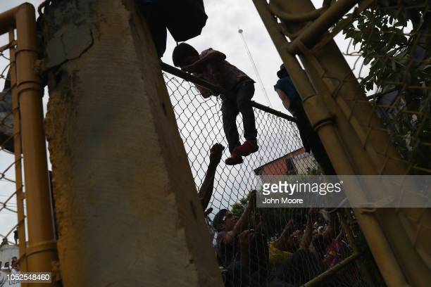 A boy in the migrant caravan climbs over a fence on the Guatemalan side of a bridge to Mexico on October 19 2018 in Ciudad Tecun Uman Guatemala The...