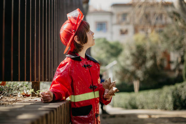 Boy in the park holding a leave and wearing a fireman costume