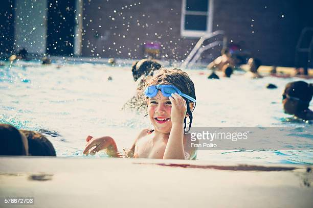 Boy in the pool smiling wearing goggles