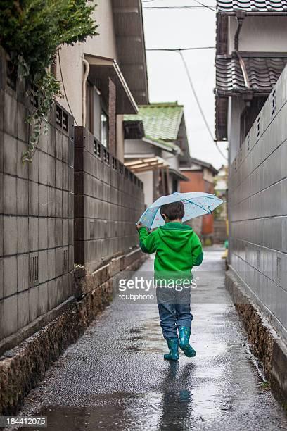 boy in the rain - レインブーツ ストックフォトと画像