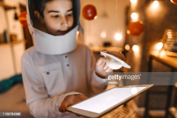 boy in the role of an astronaut with digital tablet - digital native stock pictures, royalty-free photos & images