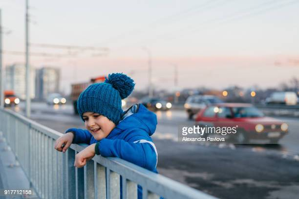 Boy in the street, traffic in the background