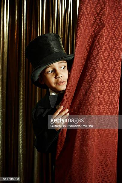 Boy in top hat behind stage curtain