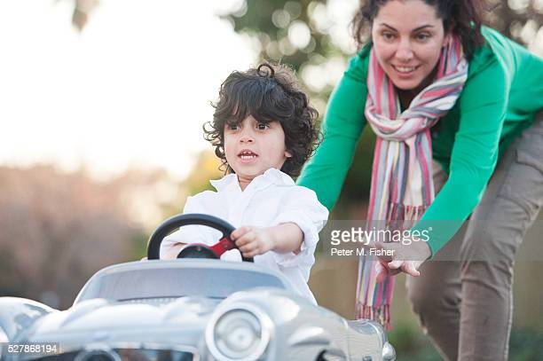 Boy (2-3) in toy car being pushed by his mother