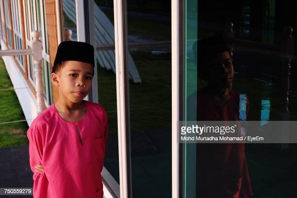 Boy In Traditional Clothing Standing By Glass Window