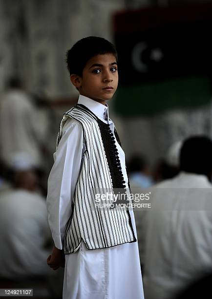 A boy in traditional dress looks on as Libyan Muslims pray in the new Mayzaram mosque in central Tripoli on August 26 on the first Friday following...