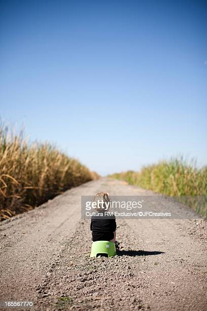 Boy in training potty on gravel road