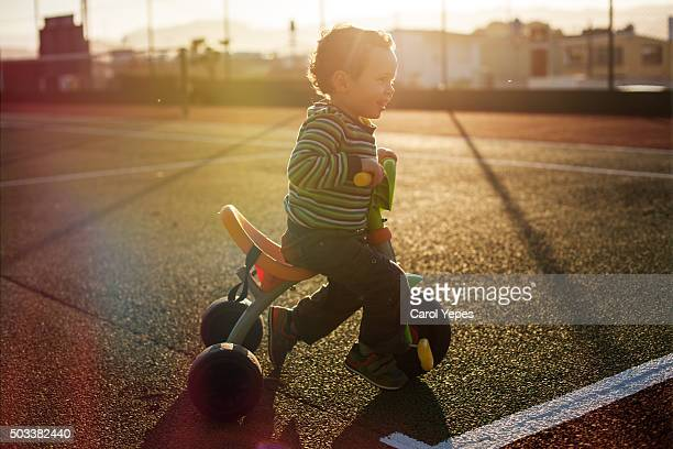 boy in tricycle  backlight side view