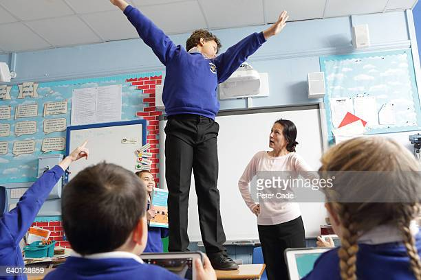 Boy in trouble for standing on table in class