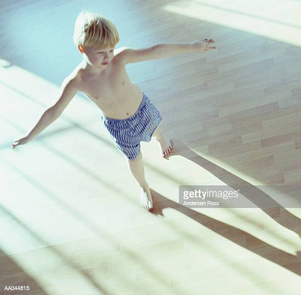 Boy (6-8) in underwear standing with arms outstretched, elevated view