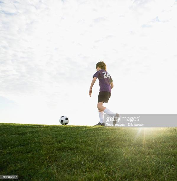 Boy in uniform kicking soccer ball