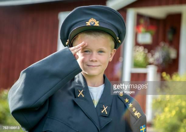 Boy in uniform saluting