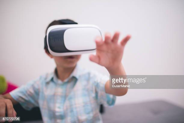 Boy in virtual reality glasses playing the game