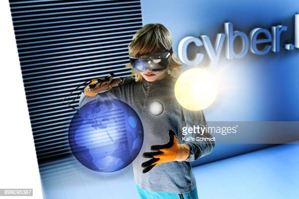 Boy in virtual reality headset interacting with floating digital earth, moon and sun