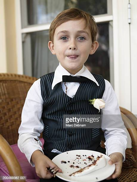 Boy (6-7) in waistcoat and bowtie holding plate, portrait