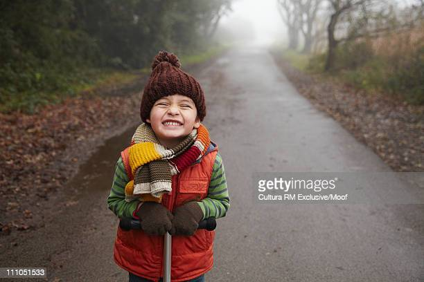Boy in warm clothes on wet path grinning